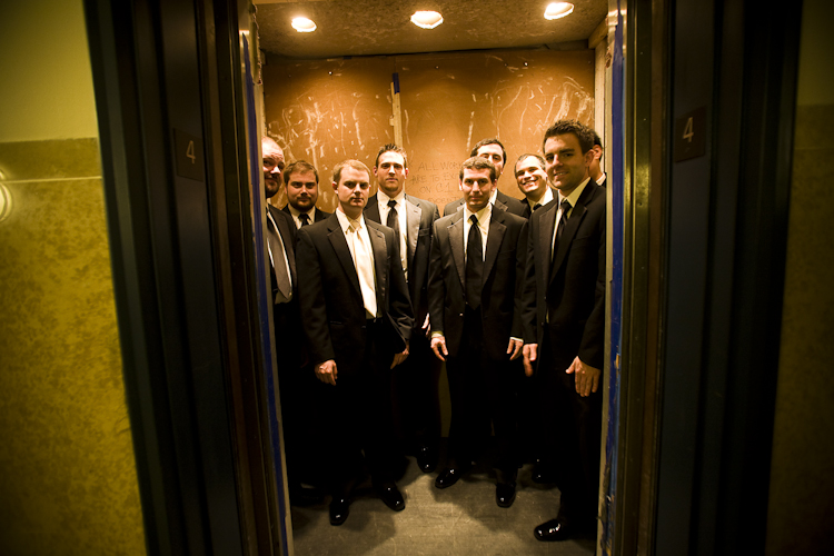 groom friends with photographer elevator
